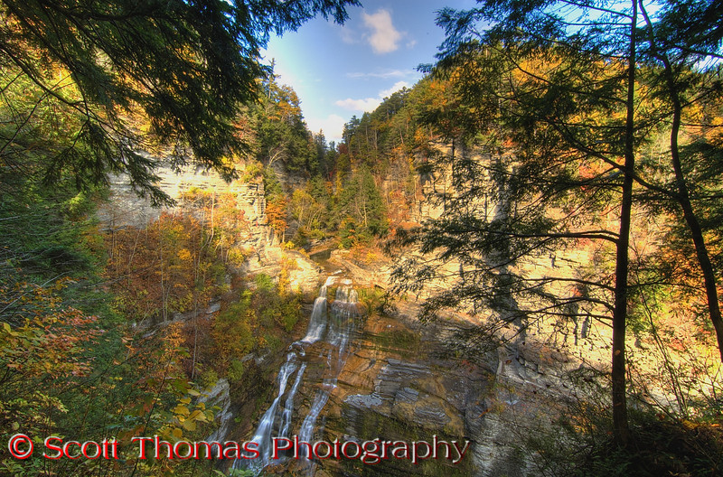 "A 20 minute drive south of Taughannock Falls, brings you to the <a href=""http://en.wikipedia.org/wiki/Robert_H._Treman_State_Park"" target=""new"">Robert H. Treman State Park</a>.  I climbed the South Rim Trail to take this photo of Lucifer Falls.  A very different waterfall.  It doesn't fall straight down but flows down 115 feet of rock and allows mosses to grow on adjacent rocks giving it a greenish tint along the edges.  The flow was low and I'll like to come back in the Spring when the flow of water is a lot heavier.  The Sun joined me on this day and HDR processing helped to balance out the large contrast where the shadow line cut through the scene.  The software didn't do as well here as the sky on the left is a bit washed out."