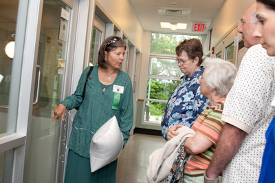 Member of the Board of Directors, Harriet DiCicco, gives a tour during the grand opening celebration. Board members, volunteers and staff alike take part not only in programming at the Potter League facility but also in outreach activities, bringing the message, mission and services of the organization to the local community.
