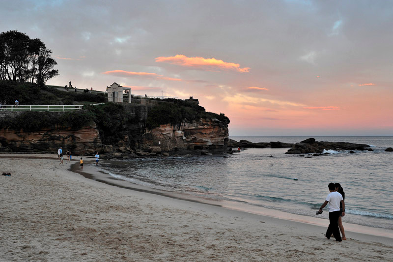 The last rays of the sun paint the distant horizon in purple. Coogee beach and the vast Pacific Ocean
