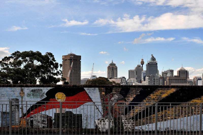 The Sydney's CBD skyline as seen above the fence near the Redfern train station. The Sydney Tower can be seen on the wall and in the distance!