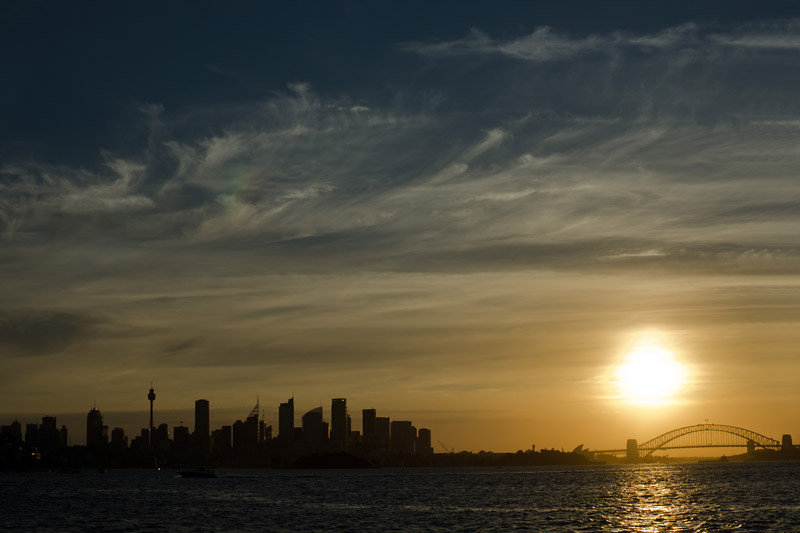 The sun is setting behind the cityscape of Sydney