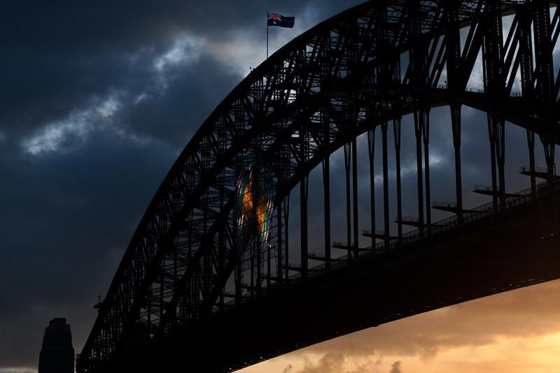 Last rays of the setting sun warming up the sky below the bridge