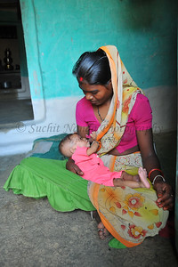 Portrait of a young mother feeding her baby at her home in a tiny village in Wardha District of Maharashtra, India.
