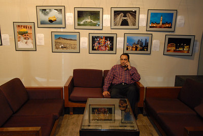 Exhibited pictures of Suchit Nanda on the wall with him in the foreground.