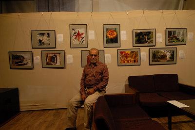 Swapan Mukherjee in front of his pictures exhibited at the Rodas Hotel, Powai, Mumbai.