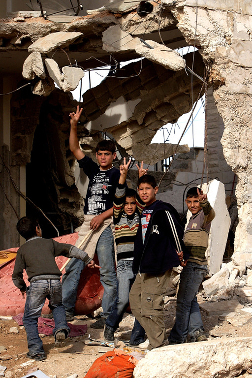 Bethlehem:  Children stand amidst the rubble of a demolished home. Just hours earlier two youths were killed and an elderly woman was left brain dead after being shot in the head by Israeli soldiers who fired at them for throwing rocks at the bulldozer.