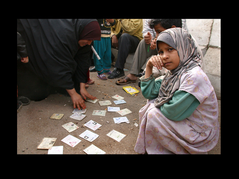 """Green Zone,"" Baghdad: A mother lays down the identification cards of family members she cannot locate.  She pleads with me to document her story. Her daughter looks intently at the camera, the pain and turmoil of her struggle evident in her eyes.  The following morning our hotel is rattled by the shockwave of a massive explosion.  A bomb had been detonated in the exact location of where this photo was taken, and where we were meant to be later that morning; 25 people were killed and nearly 100 were wounded."
