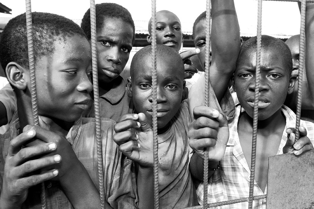 """St. Claire's Parish, Haiti: Youth wait for the younger children to finish eating so they too will be able to taste the one hot meal they will receive all week.  The pastor of the parish, Fr. Gerard (Gerry) Jean-Juste (1946 – 2009) was a charismatic and outspoken advocate for the poor.  On October 13, 2004 while serving food to approximately 600 children Fr. Gerry was arrested by heavily armed and hooded militia who fired on the children as they prayed aloud for the soldiers to release their pastor.  Three children were wounded; one was shot in the head.  Denied any medical treatment during months in prison, Fr. Gerry's health deteriorated nearly to the point of death.  He was eventually granted a """"provisional"""" release in January of 2006.  Upon his arrival at a hospital in Miami he was diagnosed with pneumonia and leukemia.  He continued to fight for justice and freedom for all Haitians despite his deteriorating health. Today, the """"What If?"""" foundation, launched by Fr. Jean-Juste and Margaret Trost, is able to provide a hot meal five days a week to over a thousand people daily, mainly children from their educational program.  <br /> """"Freedom is coming - one way or another… suffering is here, but freedom is coming! Though physical freedom is limited, the support and prayers of so many people are lifting me up. Regardless of who tries to enslave my body, my soul will taste freedom forever - and not just for me, but for all who work for justice and peace in Jesus."""" -- Father Gerard Jean-Juste (Nov. 7, 2004)"""