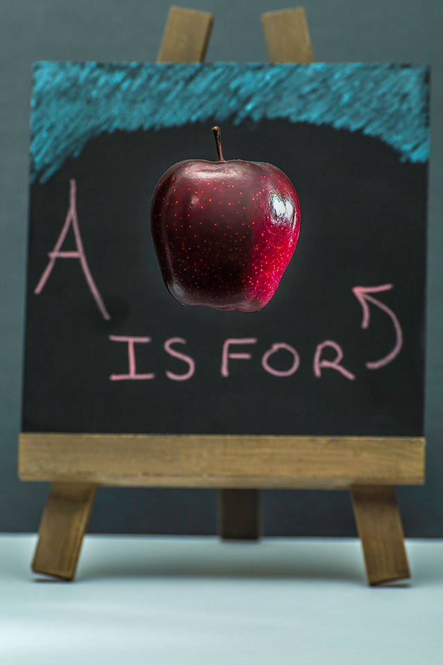 Suspended Apple in front of Chalk Board