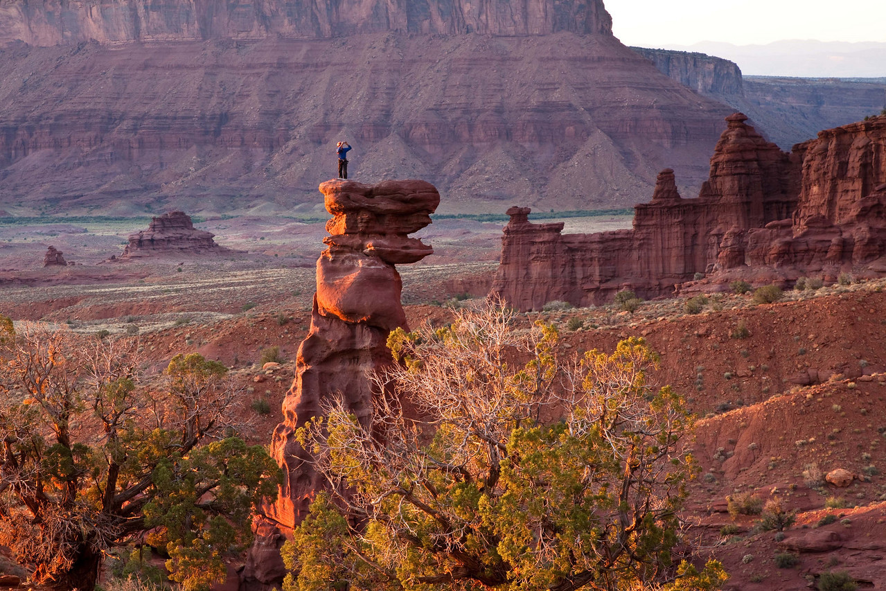 Rock climber next to Fisher Towers east of Moab