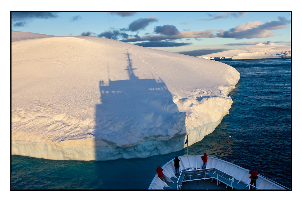 As we nosed up to this large iceberg the setting sun cast a vivid shadow on the iceberg.