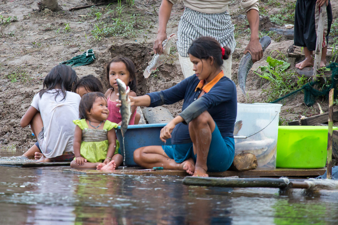 This picture symbolizes so much of the river people's lives. Mom cleaning fish with her children by her side (and another one on the way). I like the smile of the young child looking adorn fully at her mother.