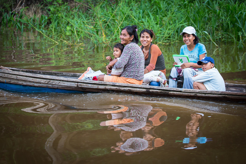 A family traveling along a small tributary. Note the computer in the hand of the woman in the blue shirt. I like the reflection too.