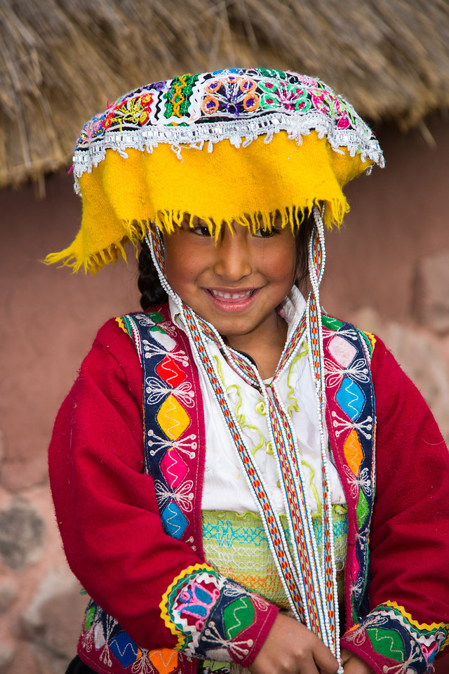 An adorable girl dressed in traditional, colorful costume
