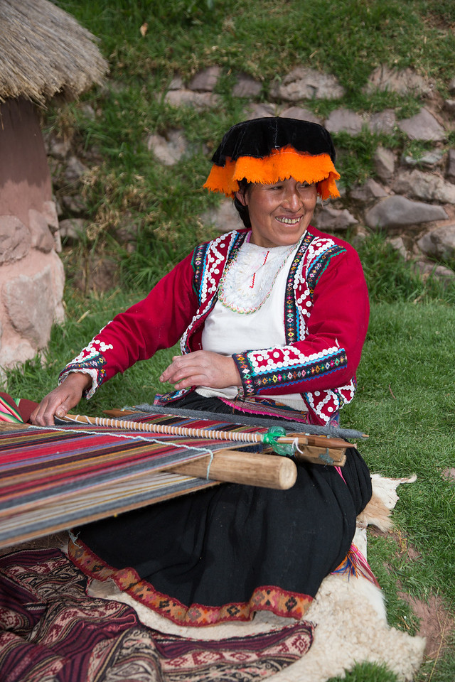 This woman, in her colorful traditional dress, was weaving a rug.