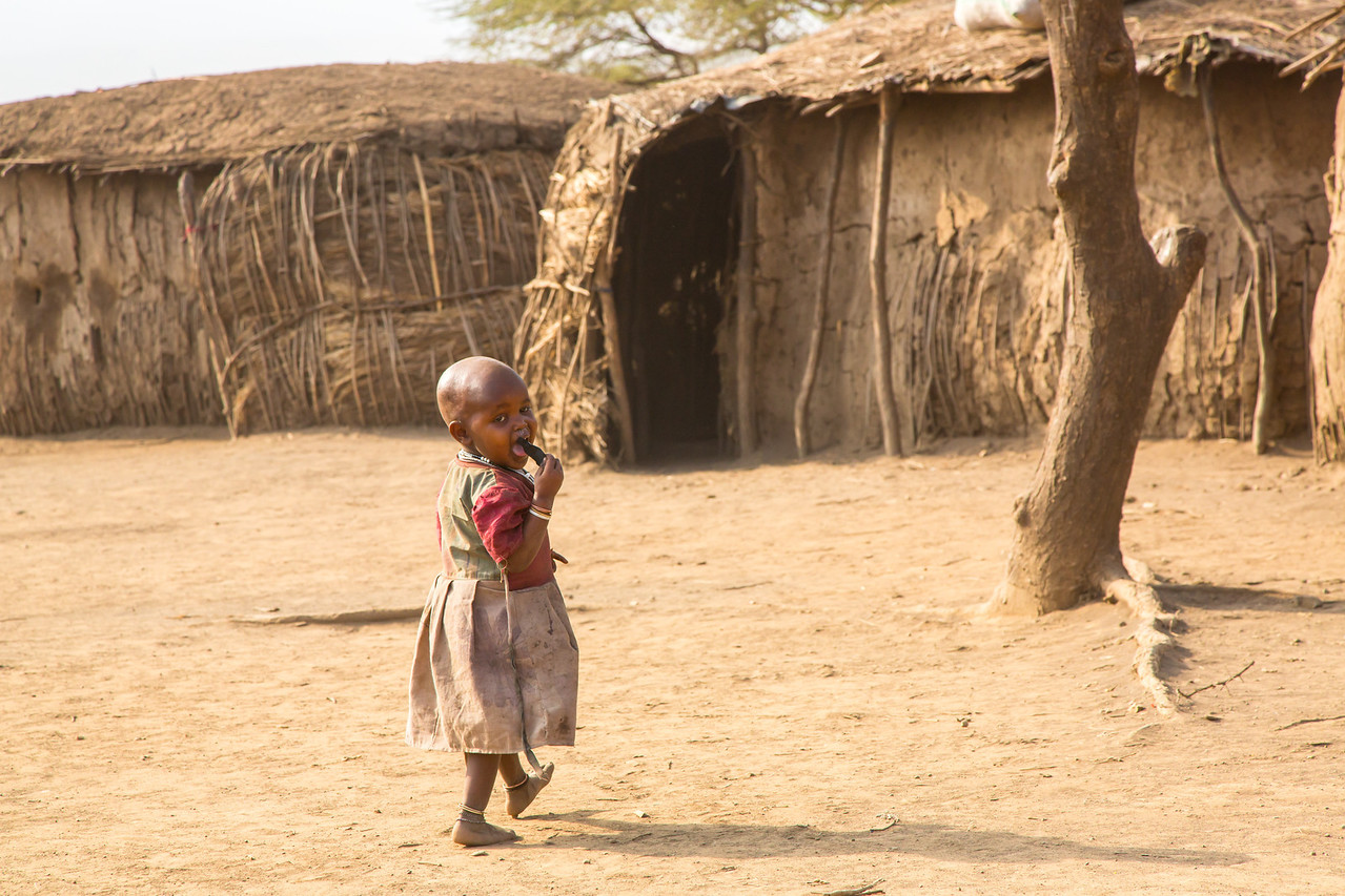 A young girl returning to her house which is called an enkaj in Swahili. Shaving the head is common.