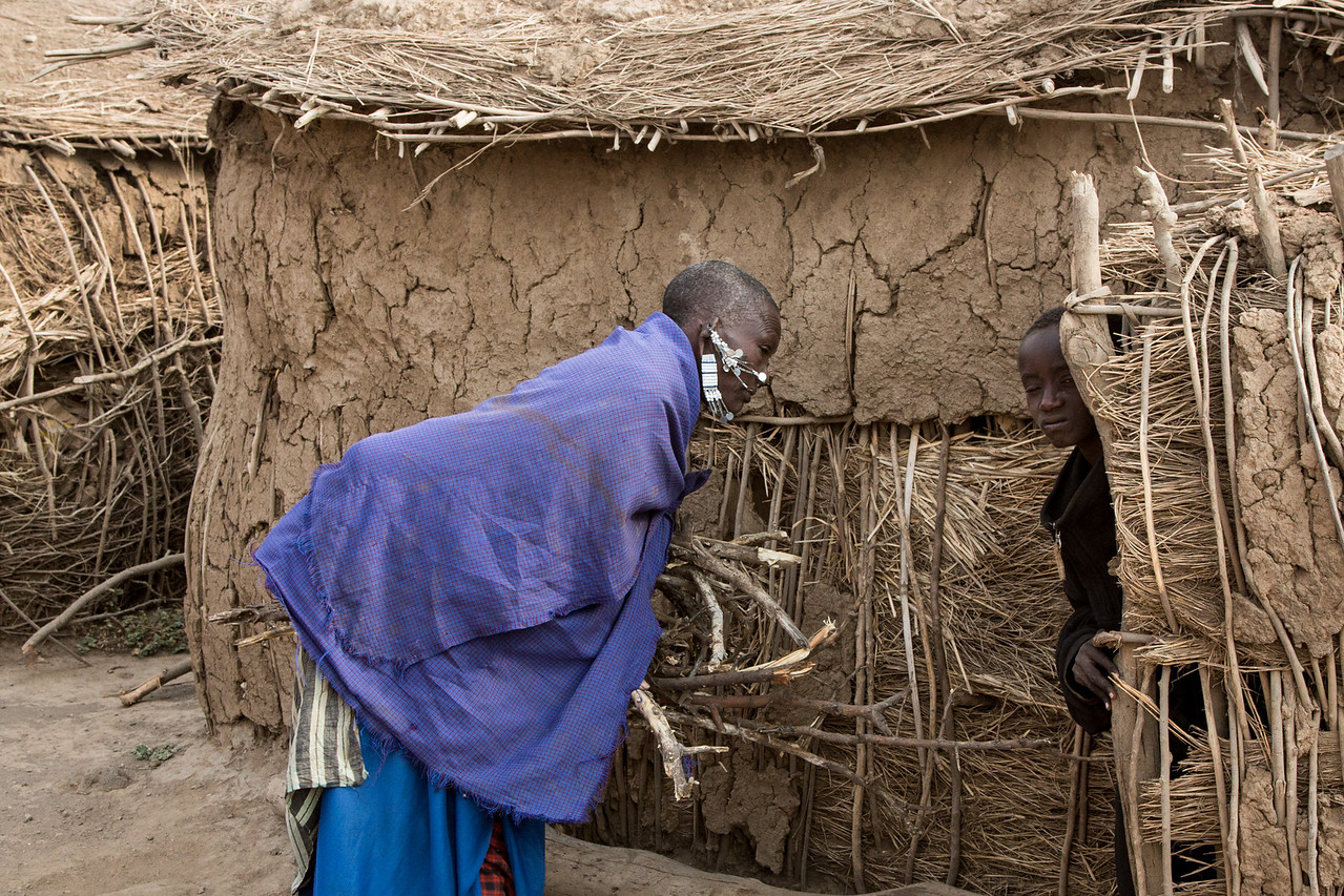 A woman bringing firewood to her Enkaj while a shy boy peeks out from the doorway.
