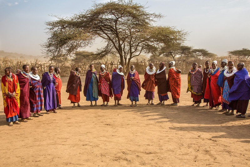 The women of the village greeted us in their colorful dress and elaborate jewelry. Observe the children on backs of the mothers. Tribal leaders encourage having as many children as possible, and the population of Masai is estimated to have doubled in the last 12 years.