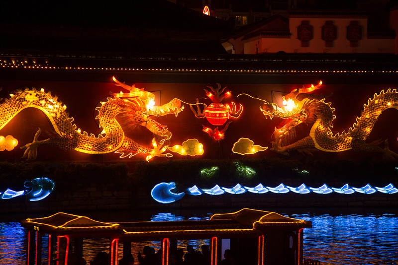 The lighted dragons illuminated the wall along the river on which small house boats cruised.