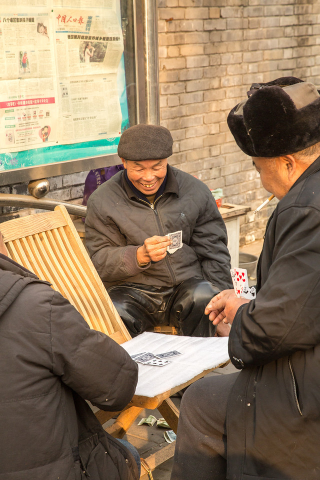 A little gambling on the street. See the money on the ground.