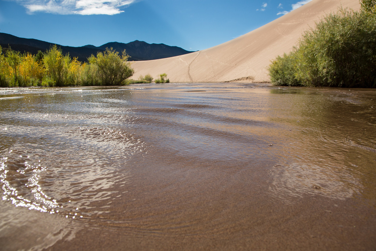 The stream recycles the sand as it waters this arid valley