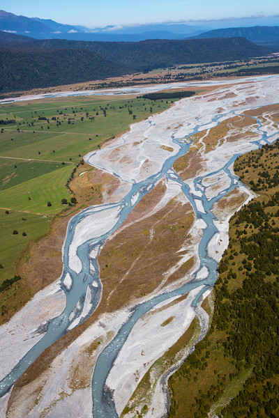 An aerial view of the glacial flow through the valley revealing its striking turquoise stream and white rocks.