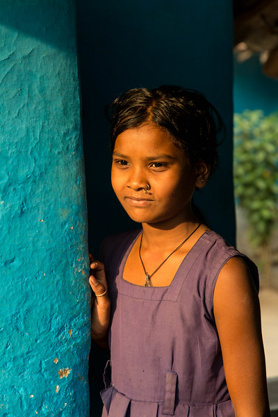 A young girl standing in the doorway with soft evening light falling on her face.