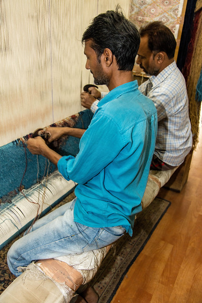 Watching carpet weavers tie knots onto the vertical strands of the loom.