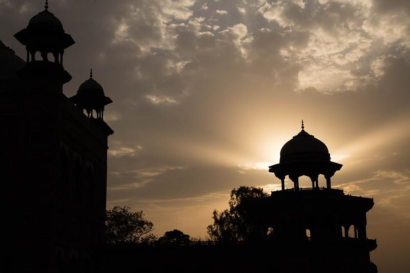 The Taj Mahal on the left and sun beams shooting through an adjacent tower.