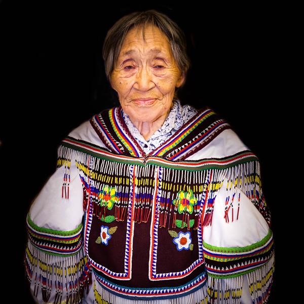 An elderly Inuit displaying the celebratory dress she made.