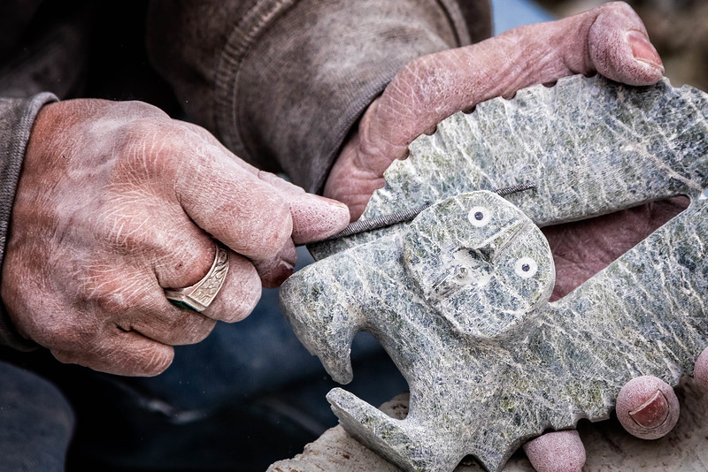 The hands of a craftsman sculpting a small Inuit symbol.