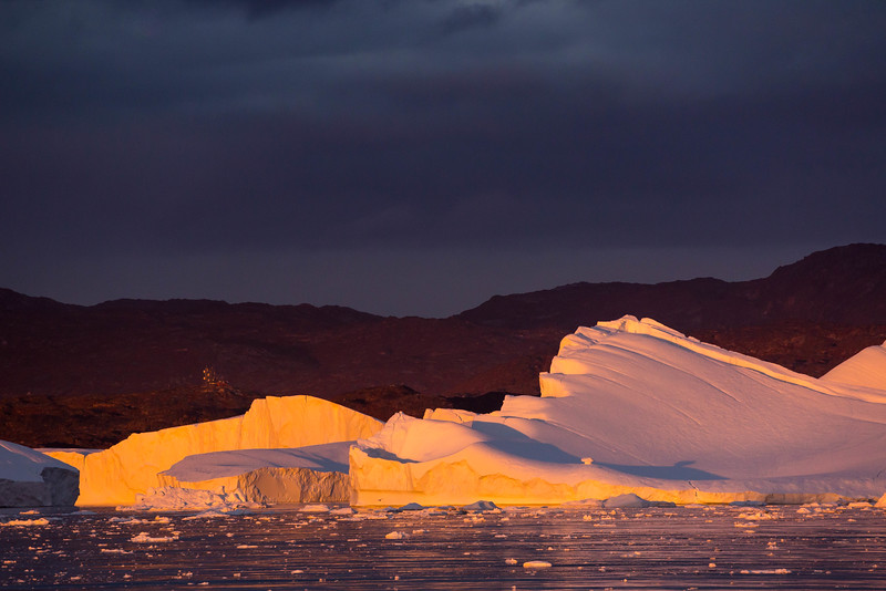 We approached Ilulissat, Greenland just as the sun was setting, making for magical light on the huge icebergs near the entrance to the harbor of the town.