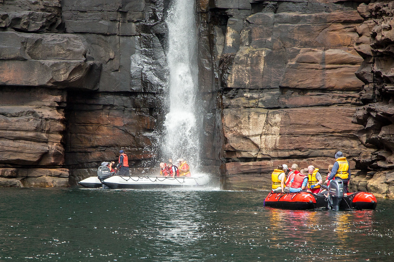 Sometimes we traveled in Zodiacs as we see here with some of our new friends getting soaked at King George Waterfall.