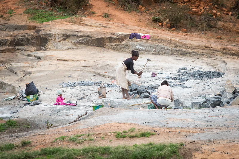 This woman was breaking up rocks into small pieces using the homemade hammer while her child watches.