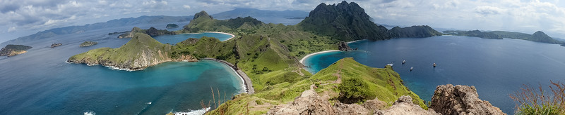 A panorama from the top of the mountain looking over the colorful land and seascapes of Indonesia.