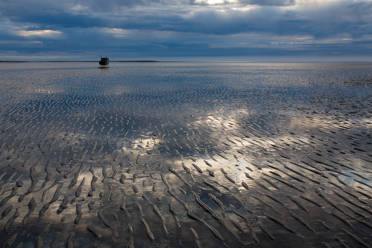 Early morning reflections in the mud flats with a grounded boat in the distance