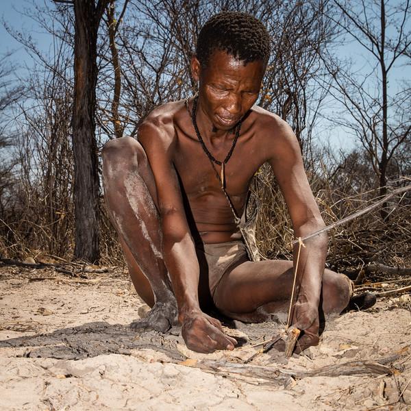 Medicine man building a snare to catch birds