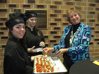 Lincoln-Way East High School students Monica Hernandez and Kara Gallagher serve hors d'oeuvres to Tinley Park-Frankfort Rotarian Karen Wegrzyn during the Club's 23rd Annual Top Ten Gala at the school Monday, March 18.