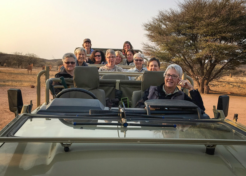 Our Group Leaving Okonjima Lodge With Our Favorite Server Riding Along Behind Karen