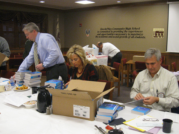 Tinley Park-Frankfort Rotary Club members Sean Brady, Janelle Witry and Steve Purucker add stickers to dictionaries that the club purchased for every third-grader in Harvey School District 152. This is the fourth year the club has donated dictionaries to Harvey students.