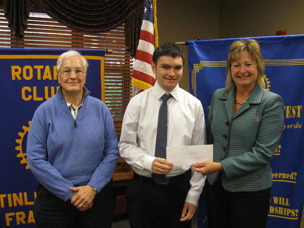 Andrew High School graduate Nicholas Lew accepts a $1,000 scholarship from Tinley Park-Frankfort Rotary Club member John Lachat and President Karen Wegrzyn.