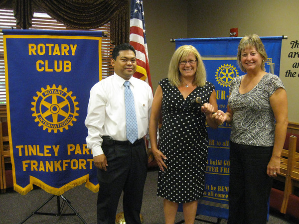 """Changing of the Guard:<br /> Tinley Park-Frankfort Rotary Club installs new president<br /> <br /> A new leader has stepped forward to guide the Tinley Park-Frankfort Rotary Club and to raise awareness about its global, national and local efforts.<br /> <br /> Margaret Semmer, a Mokena resident and parent of two students at Lincoln Way East High School, was installed July 12 as president of the Tinley Park-Frankfort Rotary Club. She replaces Karen Wegrzyn who completed her third, one-year term in June.<br /> <br /> """"I'm looking forward to continuing the efforts of the Tinley Park-Frankfort Rotary to offer scholarships to local high school students while expanding our work to serve the community,"""" said Semmer, an experienced community college educator, currently serving as Vice Chancellor of Academic Affairs at Ivy Tech Community College, Northwest Indiana.  <br /> <br /> Pictured: Karen Wegrzyn (far right), past president of the Tinley Park-Frankfort Rotary Club hands the gavel over to newly elected president, Margaret Semmer, and president-elect, Jan Paul Ferrer."""