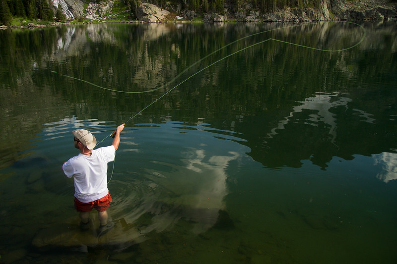 A man wadding in a high mountain lake casts his fly fishing rod.