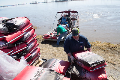 Farmers load an air boat with feed in an effort to save hogs in a barn that were surrounded by water.