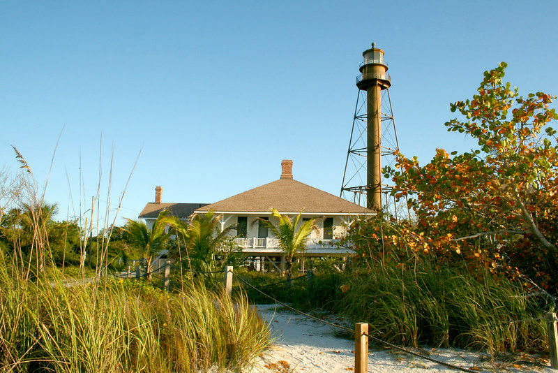 "Sanibel Lighthouse - 4/10<br /> I've been living around this area for years now and see this lighthouse all the time at the southern tip of Sanibel Island. Finally I'm getting around to photographing it. OK - Sorry if there are sooo many shots of this location - pick your favorite one and let me know! I have more but will leave it alone for now. What I will do is shoot the scene in different sky conditions as the summer comes around; clear, cloudy, sunset, stormy skies, etc... Keep coming back to see how it goes. I'm off to Boca Grande for more lighthouses tomorrow. I may have to make a ""Lighthouse"" gallery, eh?<br /> - See more in my ""Scenic"" gallery."
