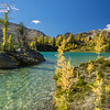 Azure Lake with golden larch trees along the shoreline in the high alpine of the Purcell Mountains.