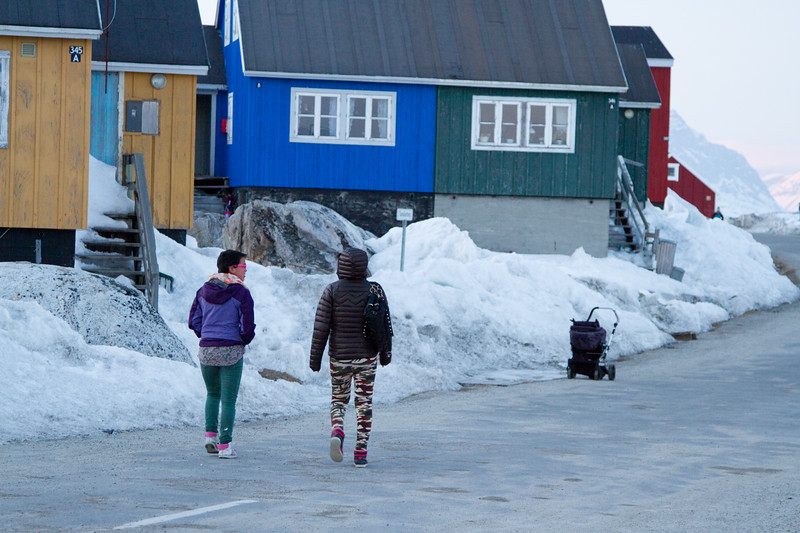 Two young girls walk down the street in Nanortalik, South Greenland.