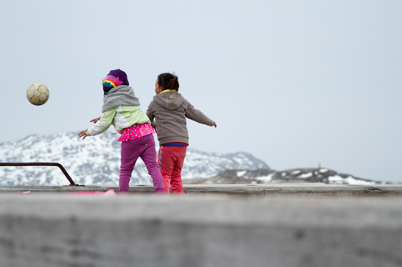 Young Greenlandic girls playing soccer on the peir in Nanortalik, South Greenland.