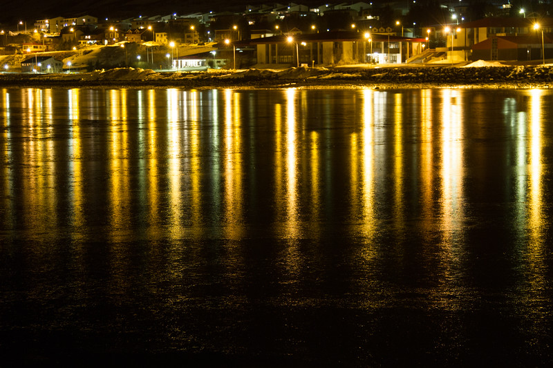 The lights of Isafjordur reflecting on the ice glazed fjord.