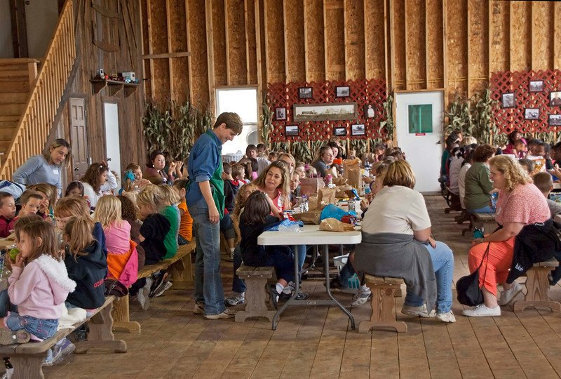 Photo: Karen Ramseyer (standing in blue) talking with a class of students and teachers visiting Ramseyer Farms near Wooster, Ohio.  Role in Wayne County's Ag-Bio Cluster: Ag-tourism venue and generator, practical agriculture education, potato and pumpkin grower, entertainment and recreation.